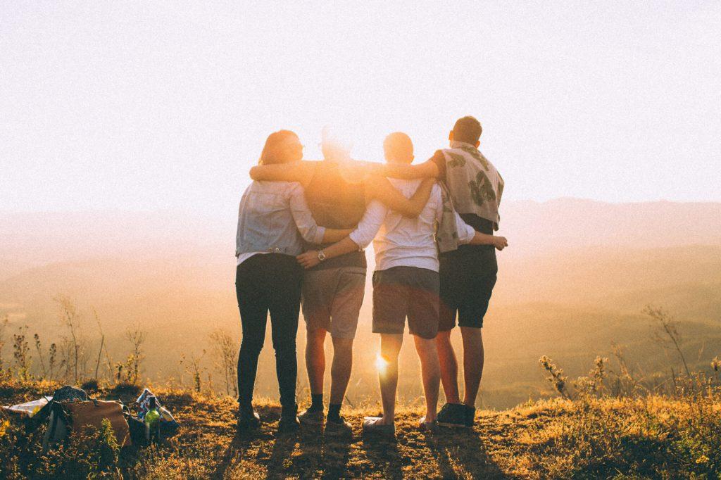 Personer står i solnedgången och håller om varandra